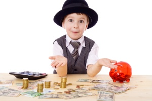 Sly boy in black hat with empty hands at the table with pile of money, isolated on white